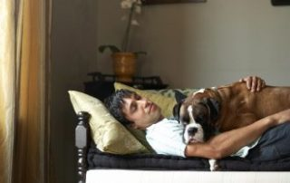man laying on sofa with his Boxer dog laying on top of him