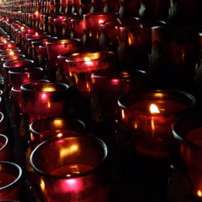 several lighted candles lined up on an alter