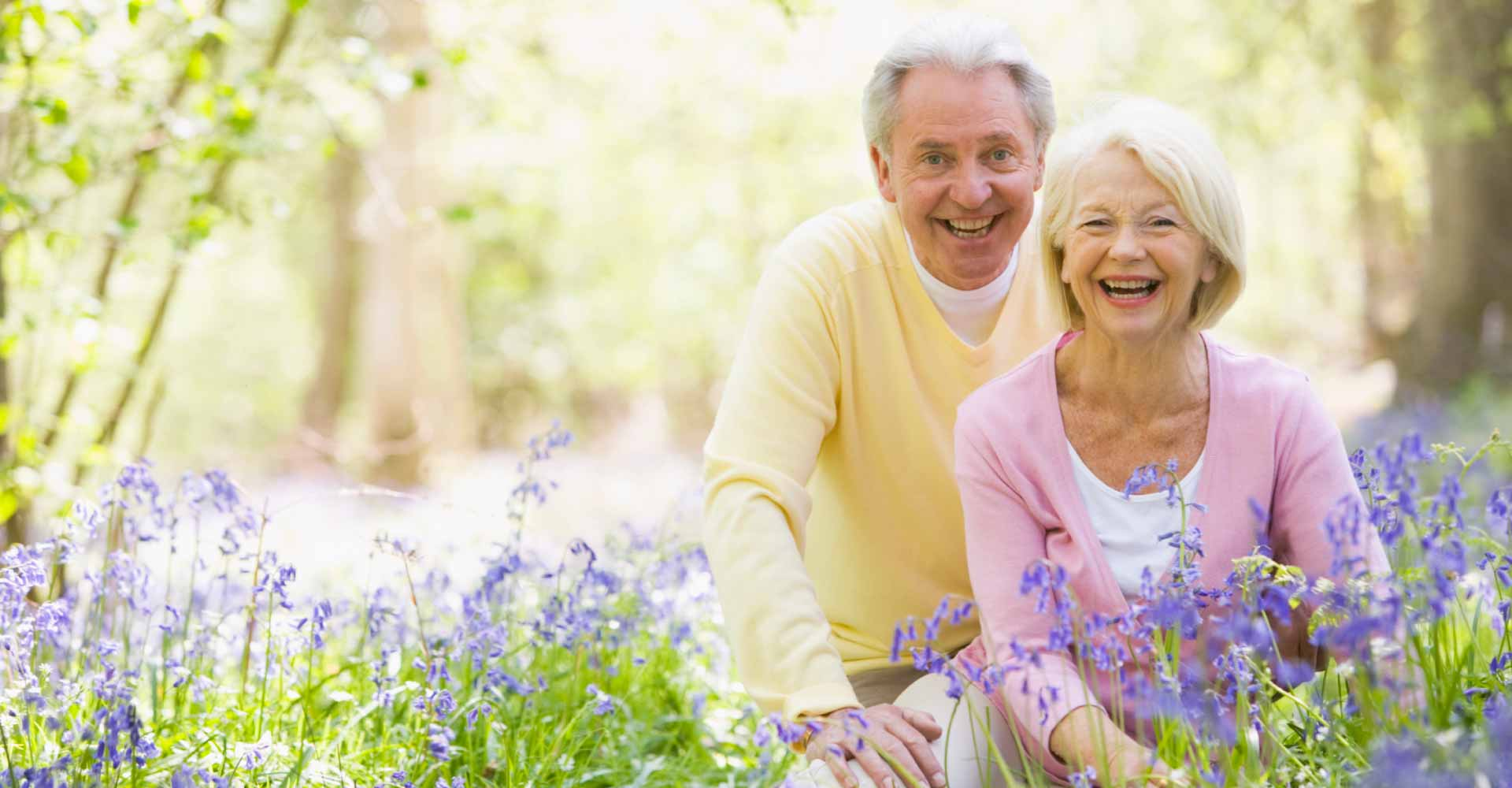 smiling elderly man and woman couple in a grassy field with purple flowers
