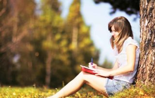 young girl in a park sitting up against a tree writing in her journal