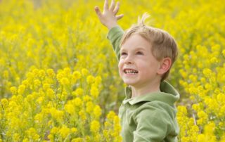 young boy playing in field of yellow flowers